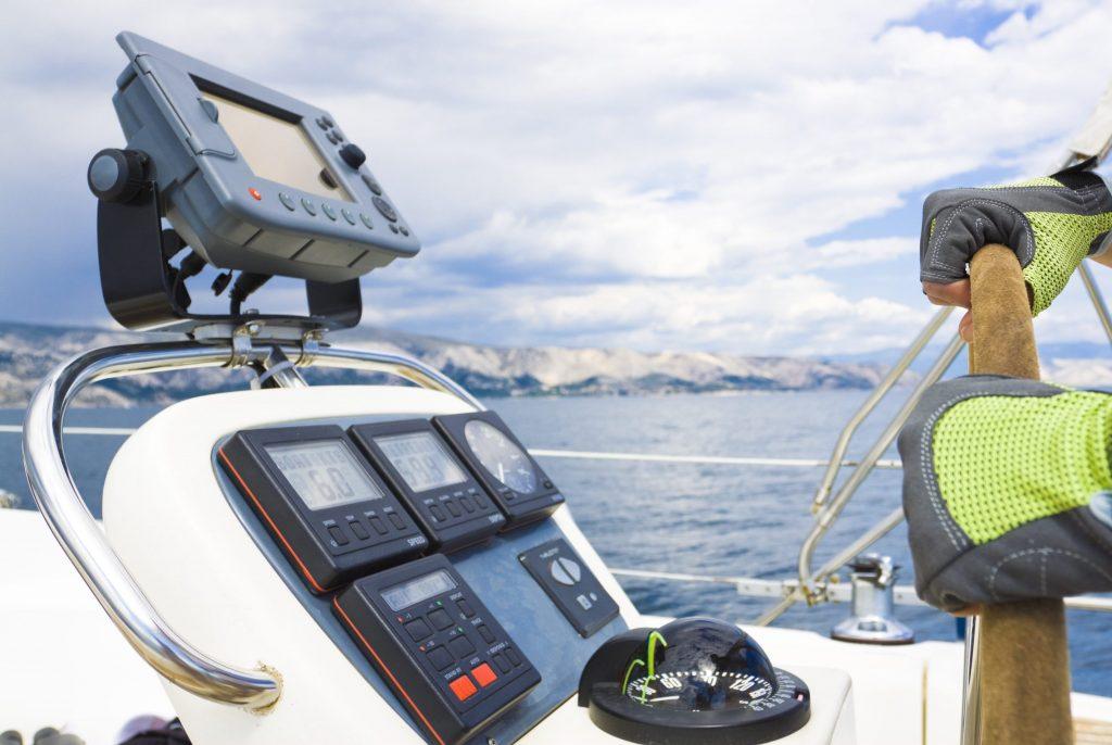 Die Steuerkonsole eines Bootes, umgeben von Wasser und am Horizont der Küstenstreifen.