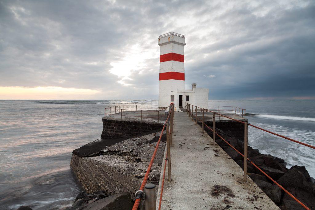Abbildung eines rot-weiß gestreiften Leuchtturms, der von Wasser umgeben ist